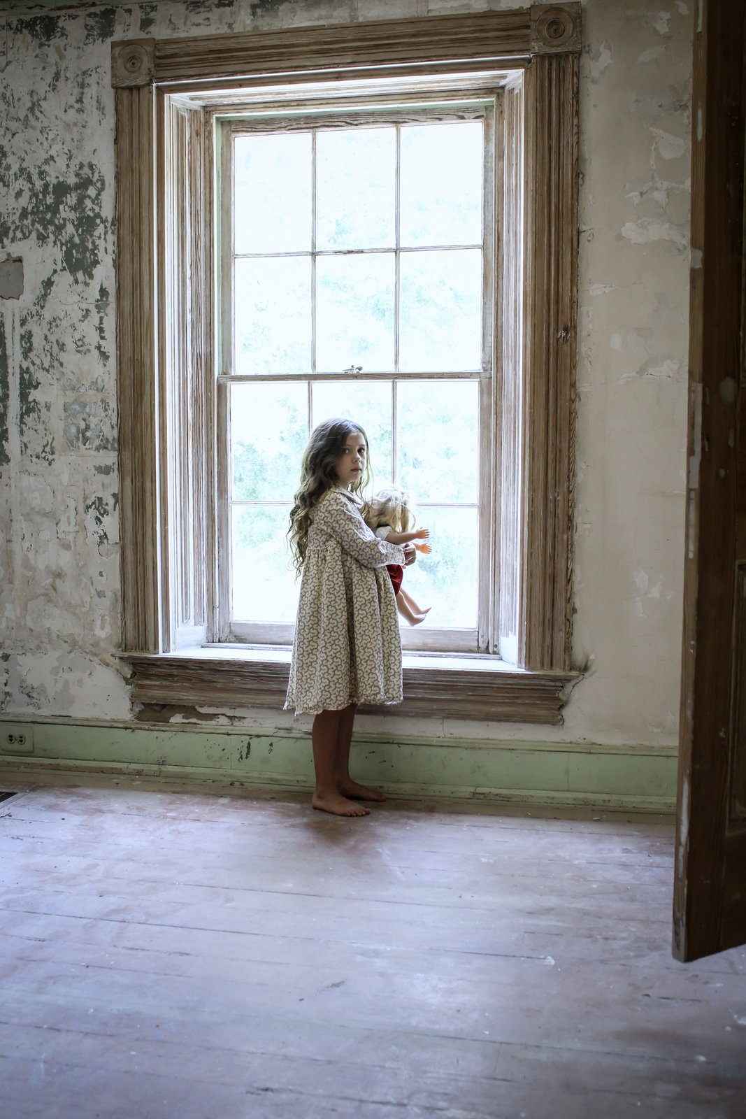 Child with Doll in Empty old room